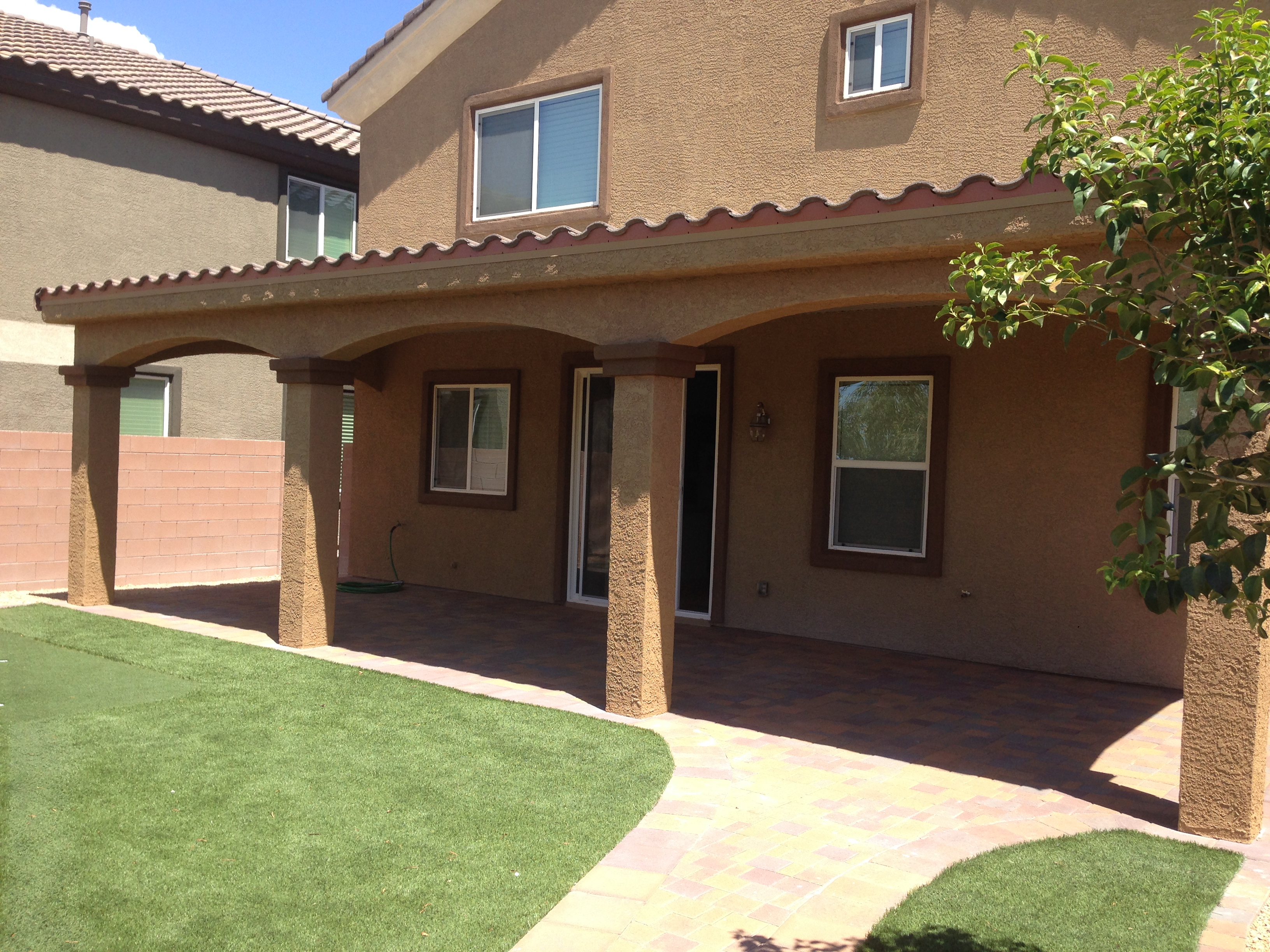 A custom patio cover with a tile roof and stucco finish.